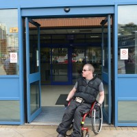 A wheelchair-using man coming out of Bromley Police Station