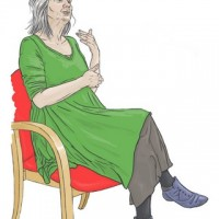A woman in a green dress, sitting in a chair and using BSL