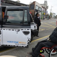 Male wheelchair user about to get into the back door of a black cab