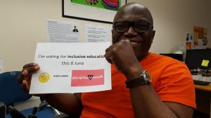 Iyiola Olafimihan holding an 'I'm voting for Inclusive Education on 8th June' sign