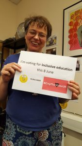 Simone Aspis holding an 'I'm voting for Inclusive Education on 8th June' sign