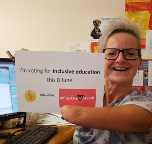 Tara Flood holding an 'I'm voting for Inclusive Education on 8th June' sign